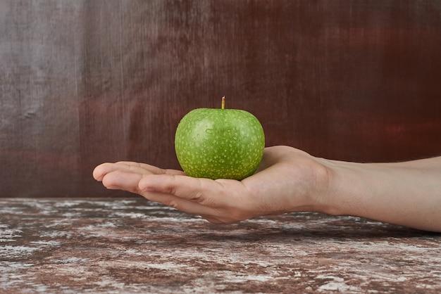 Tenendo una mela verde in mano. Foto Gratuite