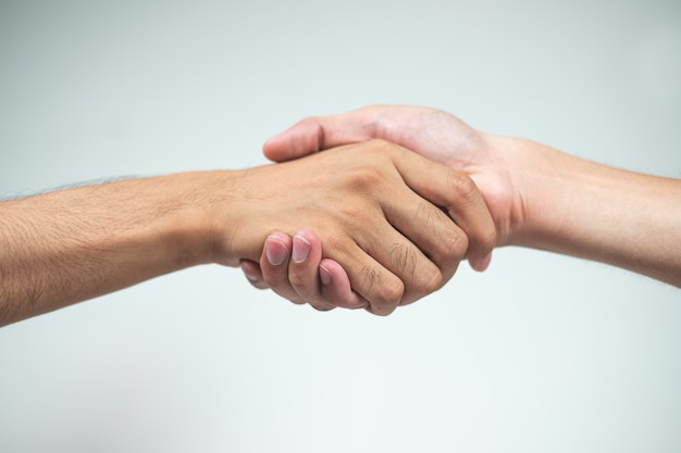 Holding hands of two men on a white surface Premium Photo