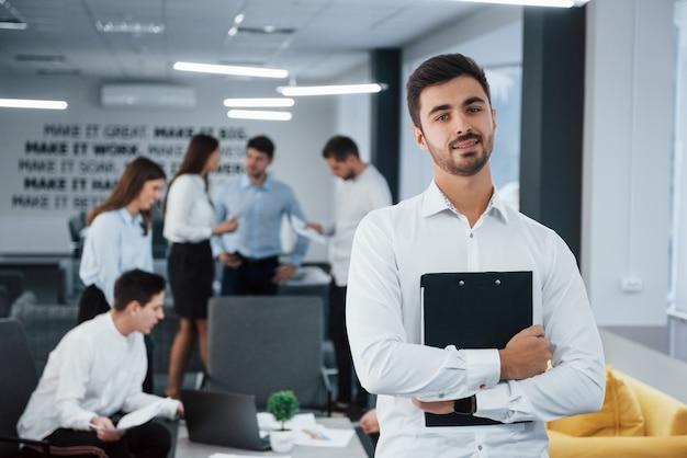 Проведение важных работ. портрет молодого парня стоит в офисе с сотрудниками на фоне Premium Фотографии