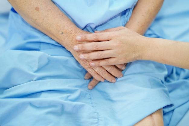 Holding touching hands asian senior or elderly old lady woman patient with love, care, helping, encourage and empathy at nursing hospital ward : healthy strong medical concept Premium Photo