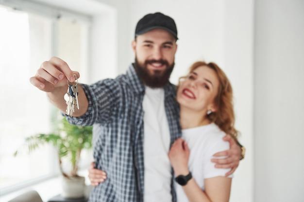 Держит ключи. счастливая пара вместе в своем новом доме. концепция переезда Бесплатные Фотографии