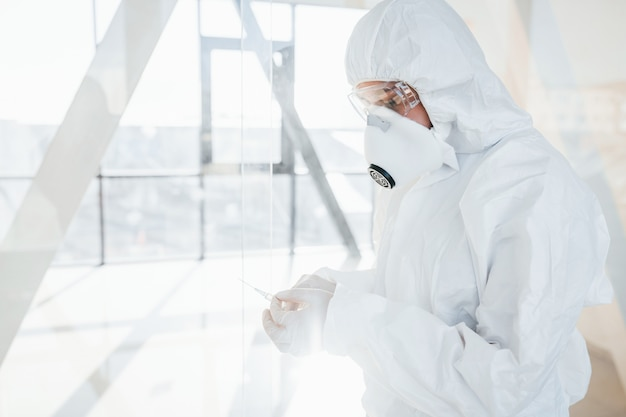 Holds syringe with medicine. female doctor scientist in lab coat, defensive eyewear and mask standing indoors Premium Photo