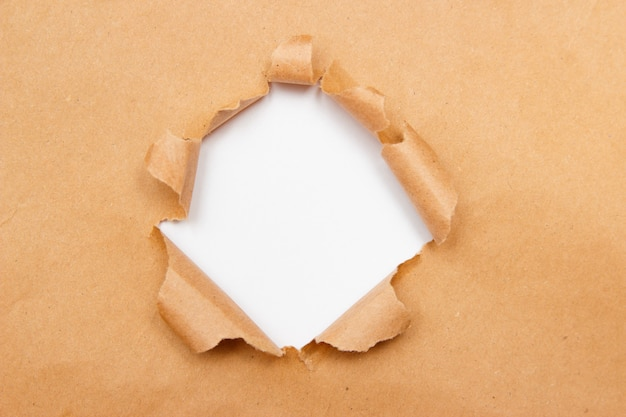 Hole into brown craft paper sheet with torn edges. Premium Photo