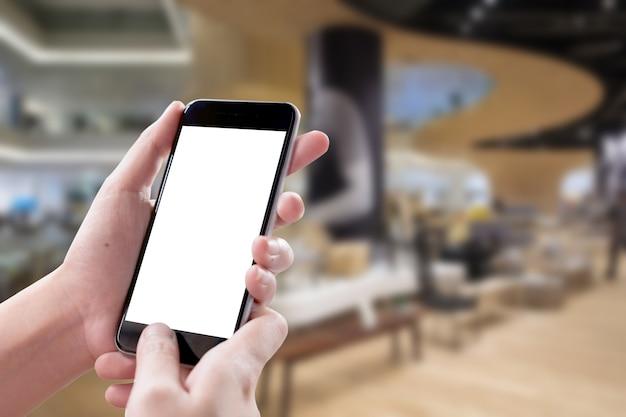 女の子のスマートフォンの空白の画面は、holelの背景がぼやけています。 Premium写真