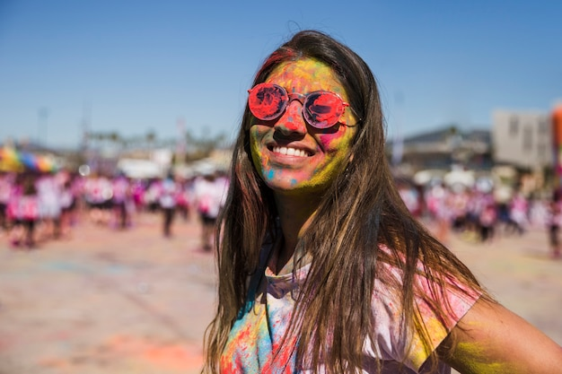 Holi color on woman's face looking at camera Free Photo