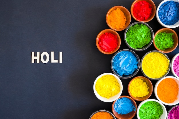 Holi text near the bowls of holi color powder on black background Free Photo