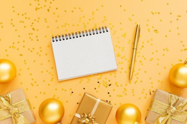 휴일 배경, 선물 상자와 반짝이 골드 크리스마스 공 골드 배경, 열린 나선형 메모장 및 펜, 평면 평신도, 평면도, 복사 공간 프리미엄 사진