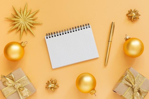 휴일 배경, 반짝이 골드 스타와 선물 상자와 크리스마스 공, 열린 나선형 메모장 및 펜, 평면 평신도, 평면도, 복사 공간 골드 배경 프리미엄 사진