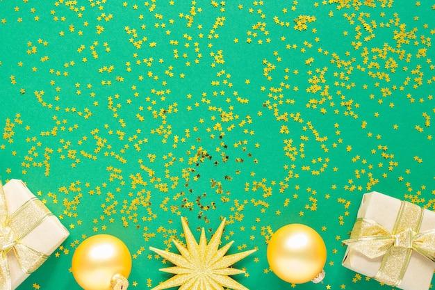 휴일 배경, 골드 크리스마스 공 및 반짝이 골드 별, 평면 평신도, 평면도와 녹색 배경에 선물 상자 프리미엄 사진
