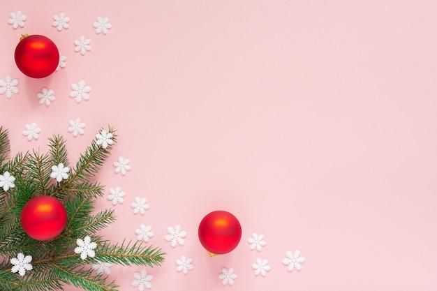 휴일 배경, 가문비 나무 가지와 눈송이, 평면 평신도, 평면도와 분홍색 배경에 크리스마스 공 프리미엄 사진