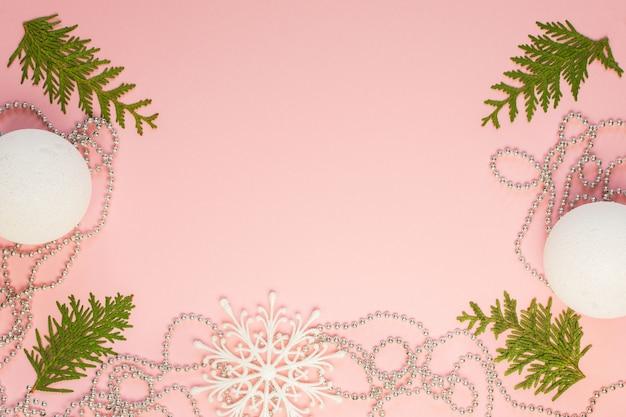 휴일 크리스마스 배경, 전나무 가지와 실버 장식 구슬, 하얀 눈송이 및 분홍색 배경에 크리스마스 공, 평면 평신도, 평면도 프리미엄 사진