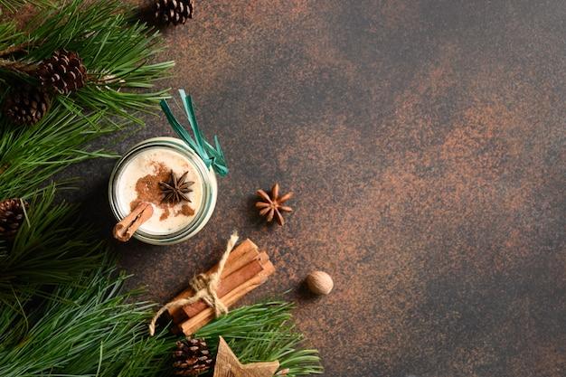茶色の背景にシナモンとアニスの星とホリデークリスマスエッグノッグ上面図コピースペース Premium写真