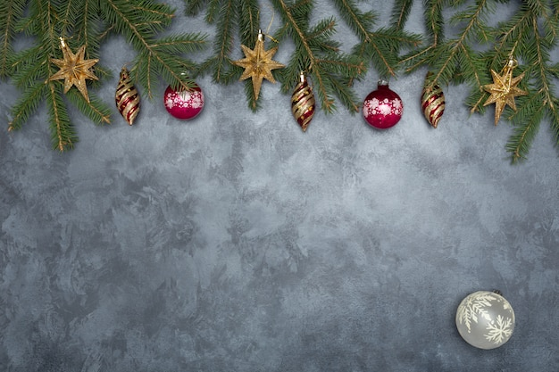 Holiday frame of christmas decorations on blue dark stucco concrete background with fir branch Premium Photo