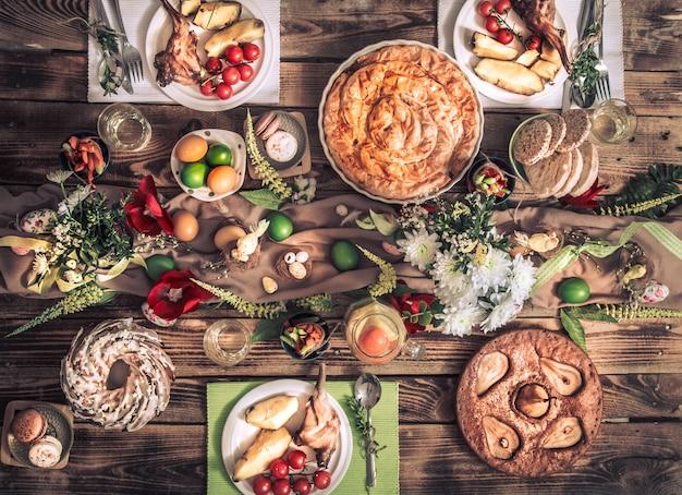 Праздничные друзья или семья за праздничным столом с мясом кролика, овощами, пирогами, яйцами, видом сверху. Premium Фотографии