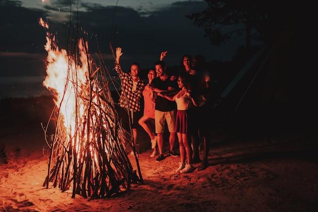 Holiday leisure company warming around bonfire on beach. Premium Photo