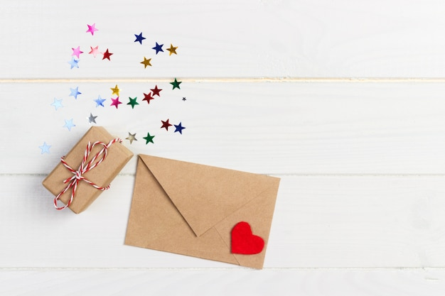 Holiday mock up: gift boxes, red heart and blank paper in brown envelope on white wooden background Premium Photo