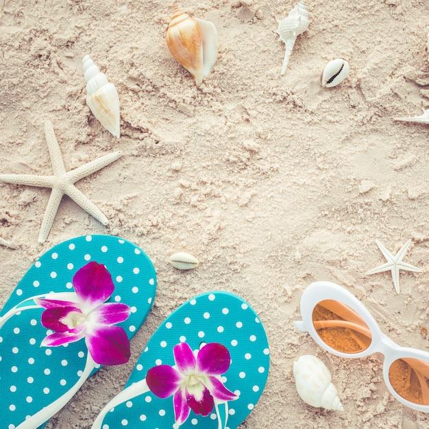 サンダルとサングラスとビーチの背景にシェルと休日の夏のコンセプト。 Premium写真