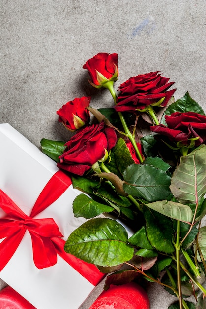 Holiday  , valentine's day. bouquet of red roses, tie with a red ribbon, with wrapped gift box and red candle. on a gray stone table,  copyspace top view Premium Photo