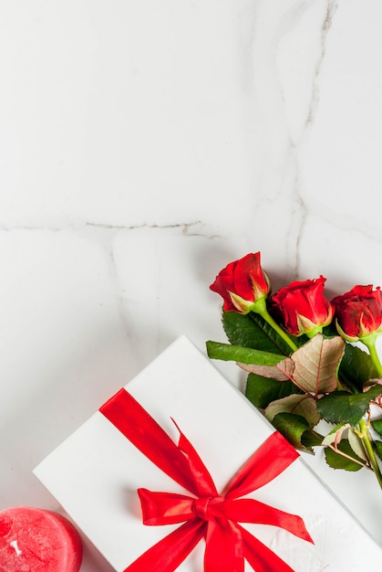 Holiday  , valentine's day. bouquet of red roses, tie with a red ribbon, with wrapped gift box. on white marble table, copyspace top view Premium Photo