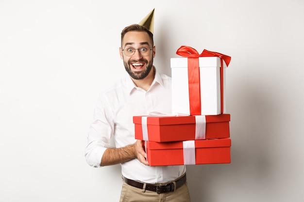 Праздники и торжества. счастливый человек получает подарки на день рождения, держит подарки и выглядит взволнованным, стоя Бесплатные Фотографии