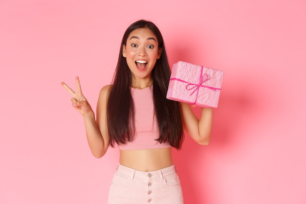 Holidays, celebration and lifestyle concept. smiling kawaii asian girl showing wrapped gift and peace gesture, likes giving presents, standing over pink background. copy space Free Photo