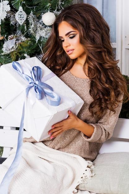 Concetto di vacanze, celebrazione e persone - donna sorridente in vestiti caldi e accoglienti che tengono il contenitore di regalo bianco sopra il fondo dell'albero di natale Foto Gratuite