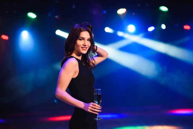 Holidays, nightlife, drinks, people and luxury concept - beautiful young woman drinking champagne at party over lights background. Premium Photo