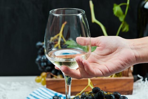 화이트 와인 한 잔을 손에 넣습니다. 무료 사진