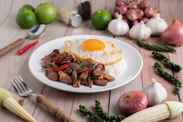 Священный базилик жареный рис с куриным сердцем и жареным яйцом на белом деревянном полу. Бесплатные Фотографии