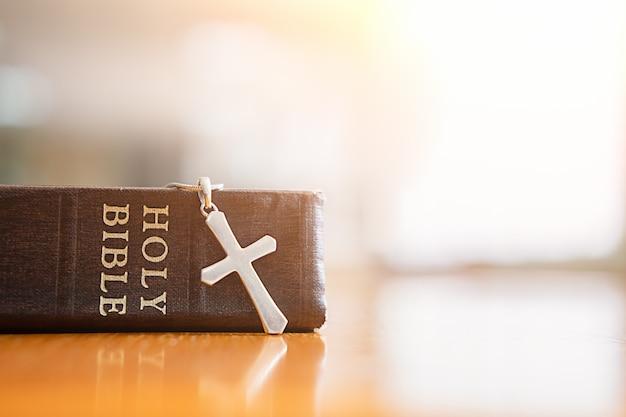성경과 테이블에 십자가. 프리미엄 사진