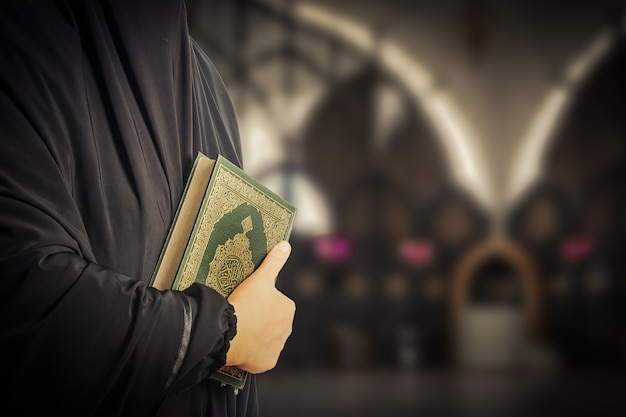 Holy book of muslims( public item of all muslims )koran in hand muslims Premium Photo