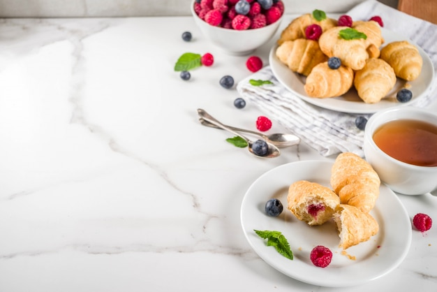 Home baked croissants with raspberries, and blueberries Premium Photo