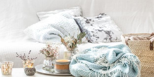 インテリアの家の装飾。ターコイズブルーの毛布と籐製のバスケットに花瓶とキャンドルの花瓶 無料写真