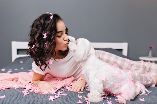 モダンなアパートメントのベッドの上のピンクのティンセルでカットブルネットの巻き毛のパジャマで若くてきれいな女性のペットと一緒に家の幸せな瞬間。白い小さな犬と一緒に自宅で身も凍るように素敵なかわいいモデル 無料写真