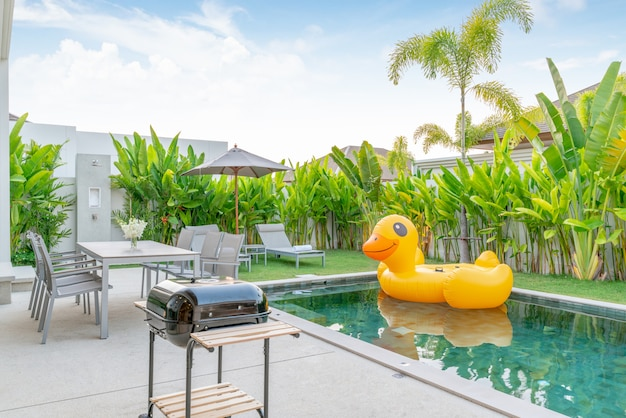 Home or house exterior design showing tropical pool villa with greenery garden, sun bed and floating duck Premium Photo
