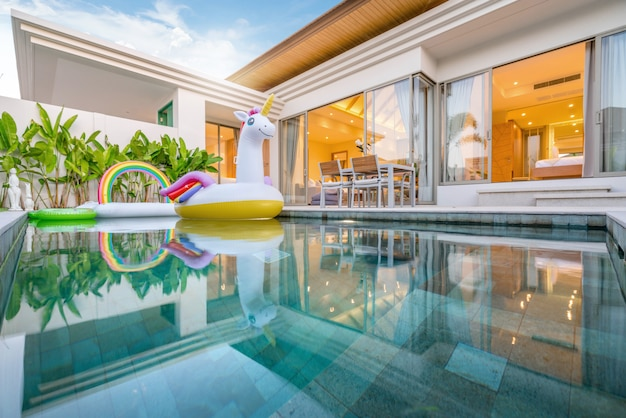 Home or house  exterior design showing tropical pool villa with greenery garden, sun bed, umbrella, pool towels and colorful floating unicorn Premium Photo