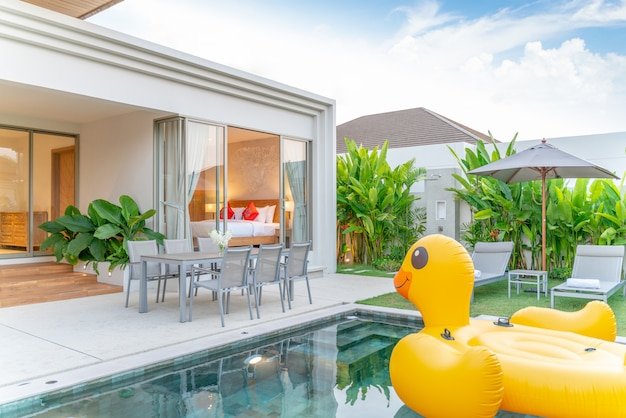 Home or house exterior design showing tropical pool villa with greenery garden, sun bed, umbrella, pool towels and floating duck Premium Photo