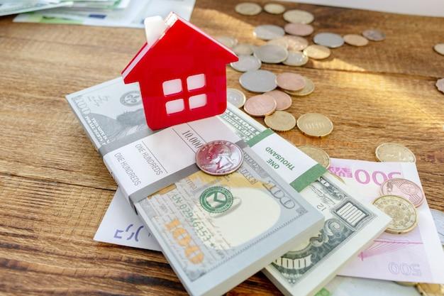 Домашний дом на фоне банкнот и монет Premium Фотографии