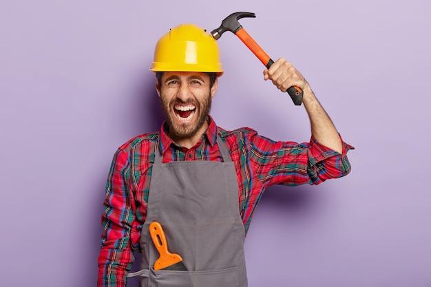 Улучшение дома, ремонт, строительство и ремонт концепции. раздраженный бригадир носит каску и держит молот, занят работой в мастерской, отрицательно кричит. опытный инженер-мужчина использует строительный инструмент Бесплатные Фотографии
