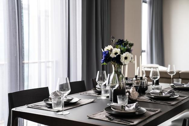 ダイニングルームのテーブルセッティングを備えたホームイニリアー、ゴールドのステンレス製食器、黒大理石のカトラリーセッティング、大理石のトップ/インテリアデザイン Premium写真