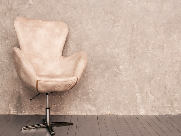 Home interior gray wall background with beige velvet armchair and wooden floor Free Photo