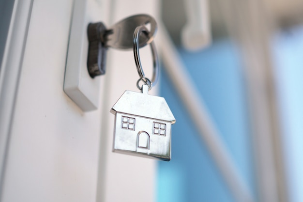 Home key for unlocking the new house door. renting, buying, selling houses Premium Photo