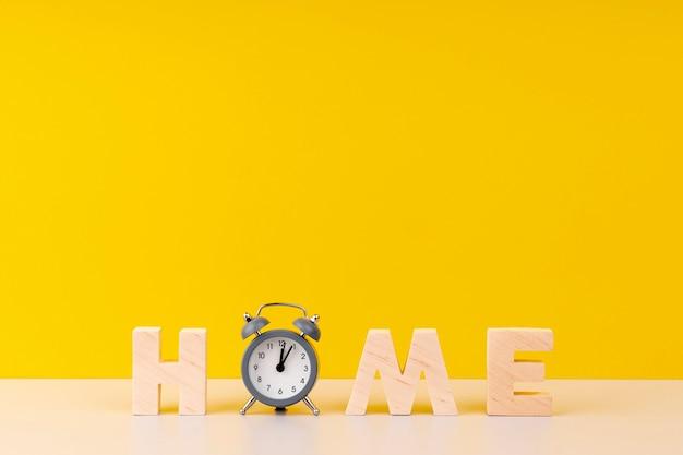 Домашняя надпись с деревянными буквами и часами на желтом фоне Premium Фотографии
