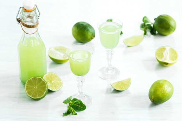 Home lime liquor in a glass and fresh lemons and limes on white Free Photo