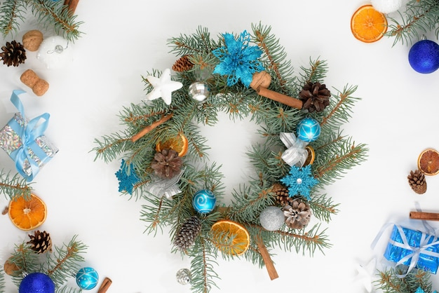 집에서 만든 크리스마스 트리 화 환은 2021 황소의 색상에 파란색과 은색 공이있는 가벼운 나무 벽에 전나무 가지로 만들어졌습니다. 프리미엄 사진