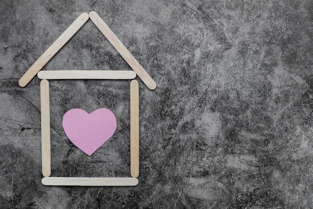 La casa fatta dai bastoni di gelato di legno con forma del cuore sulla parete nera del grunge Foto Gratuite