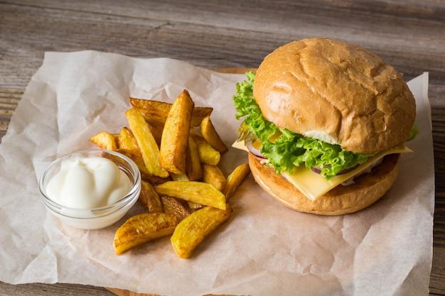 自家製ハンバーガー、チキン、オニオン、キュウリ、レタス、チーズ、ポテトフライ付きの木製テーブル Premium写真