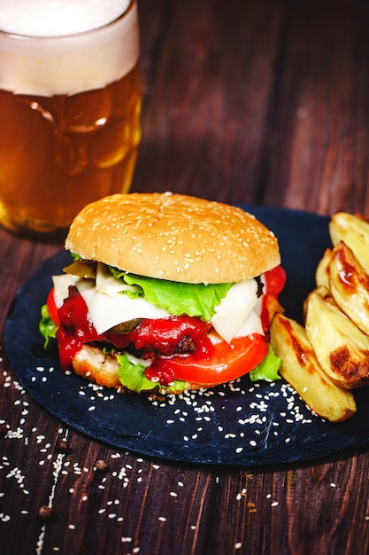 Home made mouth-watering, delicious beef burger with lettuce and potato, glass of beer served on stone cutting board. dark Premium Photo