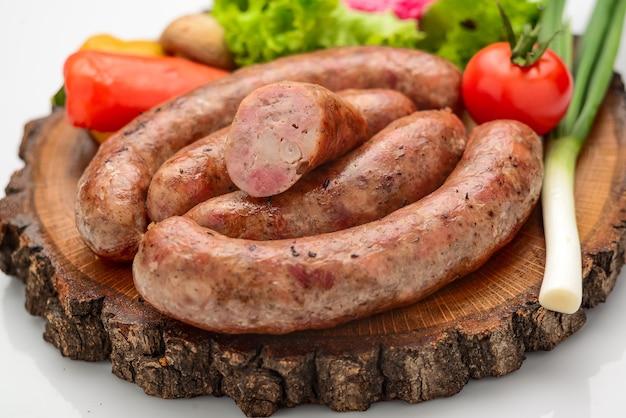 Домашняя колбаса с овощами на деревянной доске Premium Фотографии