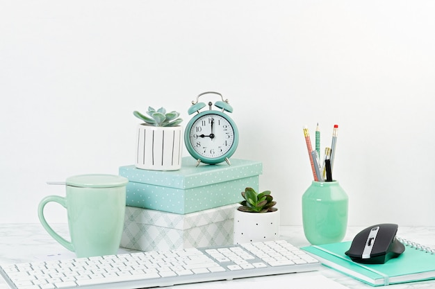 Home office concept with flowers in the pots and office supply, computer keyboard and mouse Premium Photo
